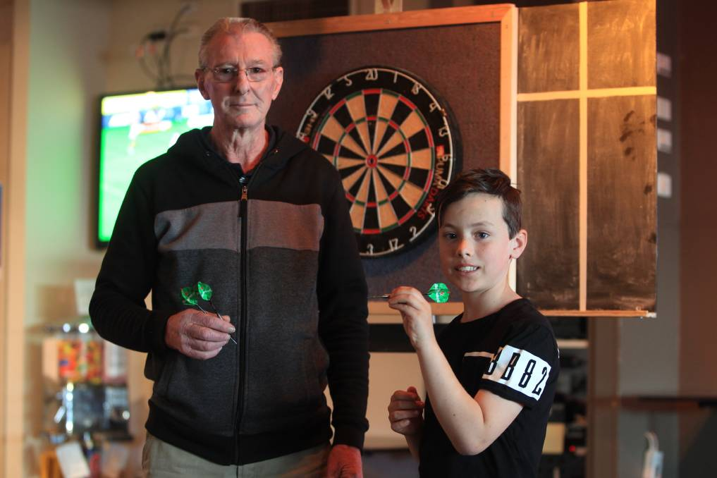 Peter Deery (left) is excited to teach darts to youngsters like Mason Smith at the Camden RSL Club. Picture: Simon Bennett
