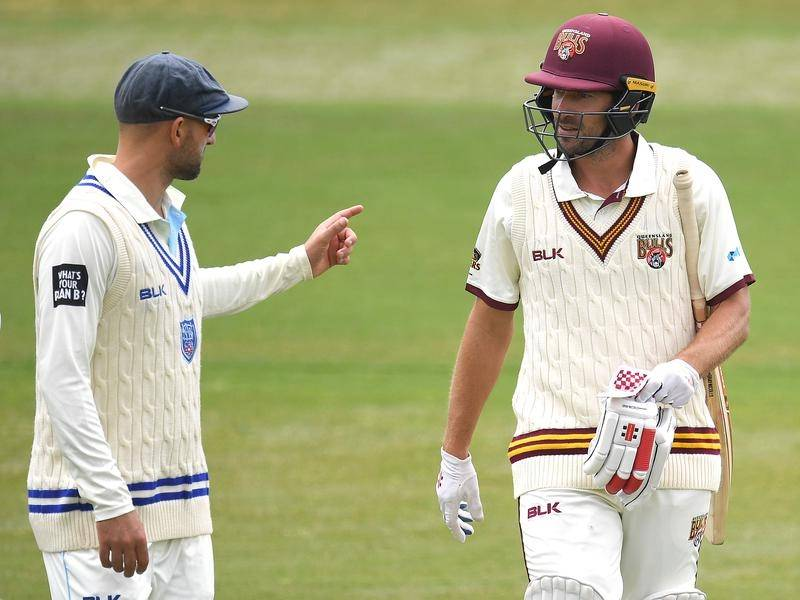 Joe Burns (r) aims to get on top off Nathan Lyon (l) when Queensland meet NSW in the Shield final.